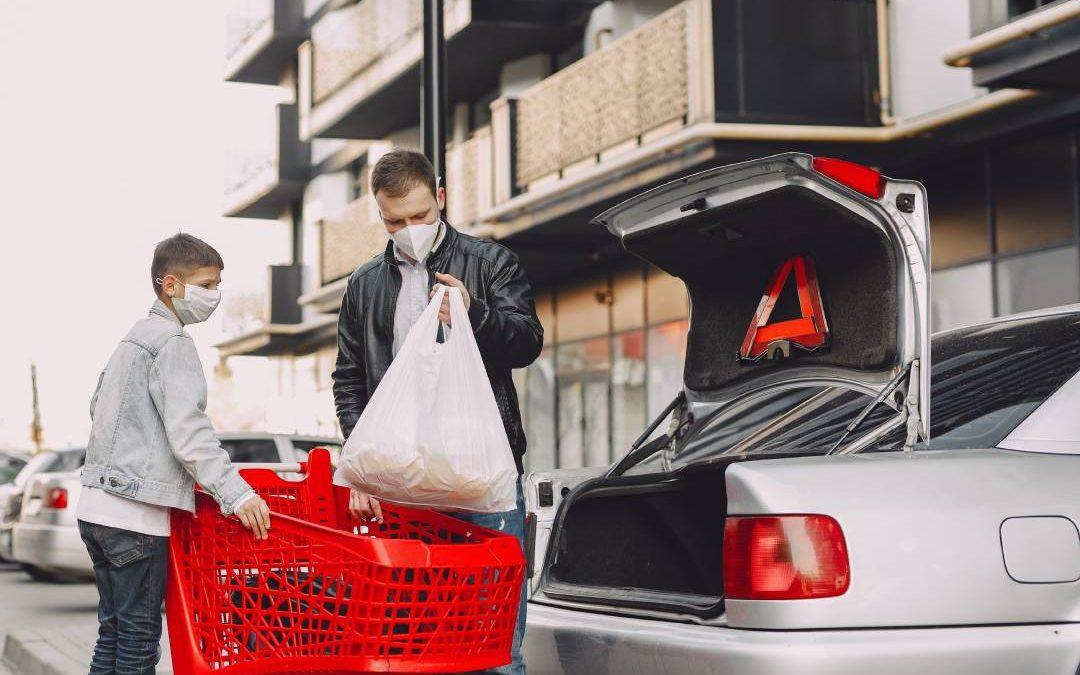 Due persone con le mascherine che caricano la spesa in auto durante il Coronavirus